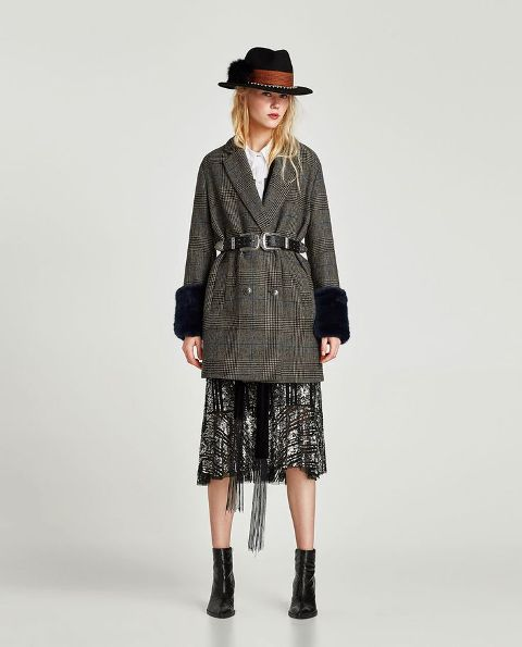 With white shirt, wide brim hat, black belt, leather boots and printed skirt