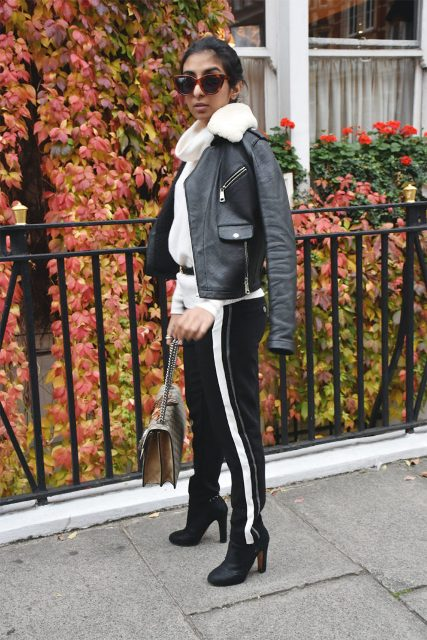 With white turtleneck, black belt, chain strap bag, leather jacket and high heeled boots