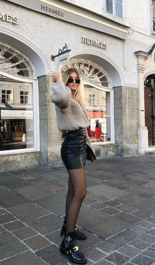 a black leather mini skirt, a grey chunky knit sweater, black tights and cool boots with belts
