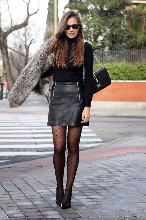 a black turtleneck, a black leather mini with zips, black printed tights and shoes, a black bag and a grey fur jacket