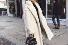 a black turtleneck, black skinnies, white trainers, a white faux fur coat and a printed black bag