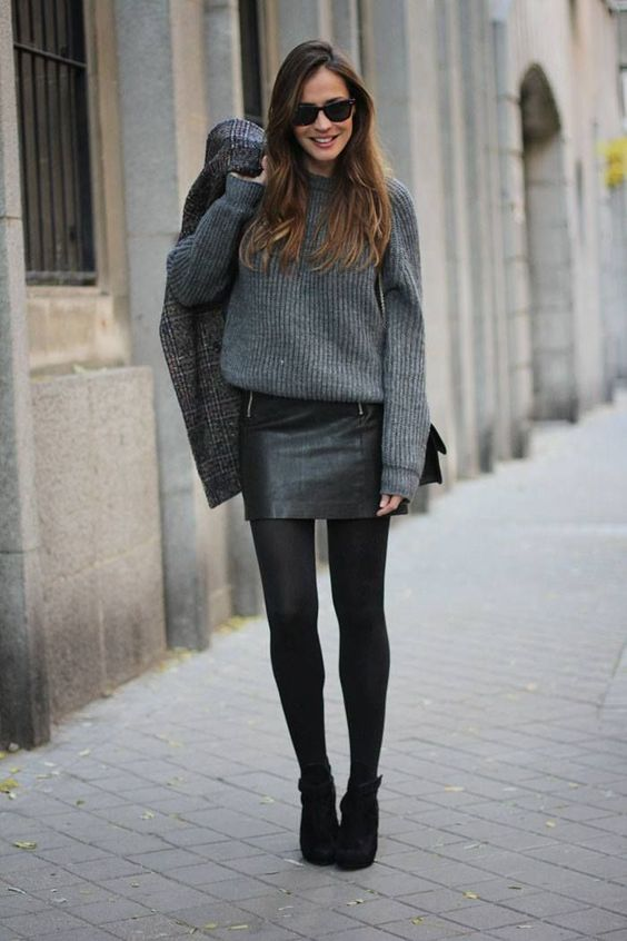 a grey oversized sweater, a black leather mini skirt, black tights and booties, a plaid coat