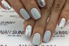 a holiday or wedding manicure with shiny grey nails accented with rhinestones and silver glitter nails