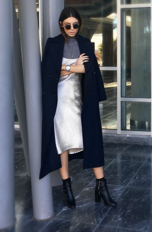 a layered outfit with a grey turtleneck, a white slip knee dress, a navy coat and black booties