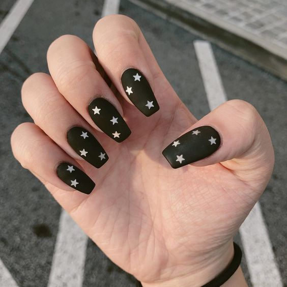 a matte black manicure with nude stars will make your look whimsier and cooler