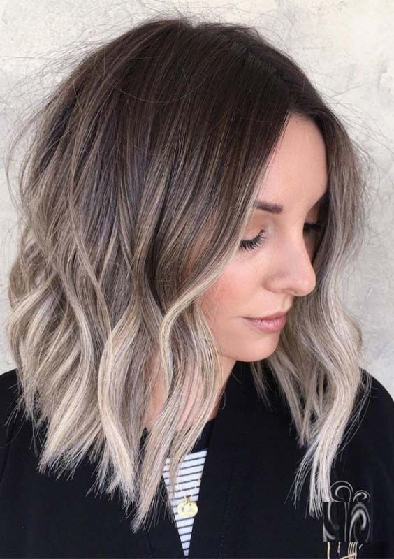 a medium length haircut with waves and a slight mushroom blond balayage plus a darker root for a trendy touch