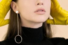 a minimalist mono earring with a large white bead, a bar and a circle for a statement