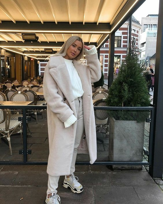 a neutral winter look with a white sweater, white jeans, neutral trainers and a faux fur midi coat