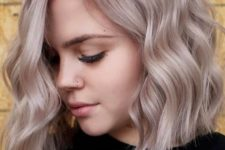 a non-traditional bob with waves and done in mushroom blond is a bold and chic idea with much volume