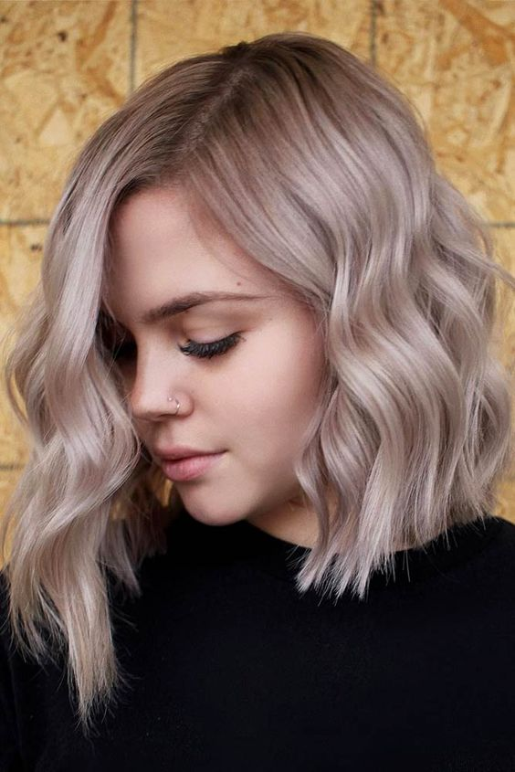 a non traditional bob with waves and done in mushroom blond is a bold and chic idea with much volume