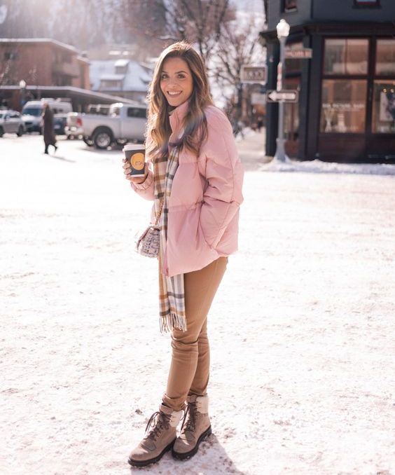 a pink puff jacket, a plaid scarf, tan jeans and beige hiking boots for a glam winter look