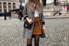 a printed tee, a rust suede mini skirt with a ring sash, a plaid coat, black booties and a blakc crossbody