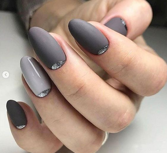 a shiny and matte manicure done in several shades of grey and with silver glitter touches just wows