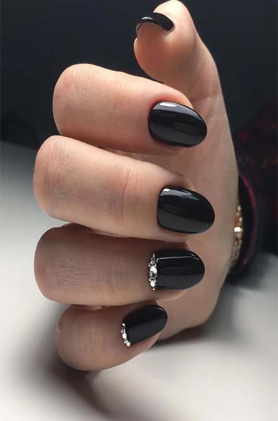 a shiny black manicure accented with rhinstones is a chic and bright idea for winter holiday parties