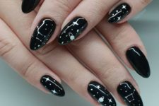a shiny black manicure with white celestial art and detailing for a trendy celestial-inspired look