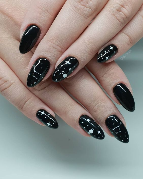 a shiny black manicure with white celestial art and detailing for a trendy celestial inspired look