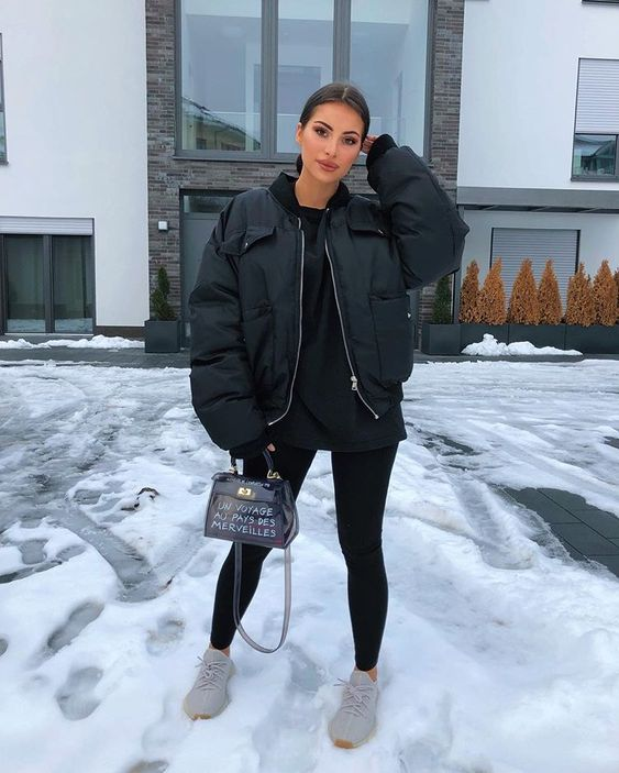 a sporty winter outfit with a black hoodie, leggings, a padded bomber jacket, grey trainers and a printed bag