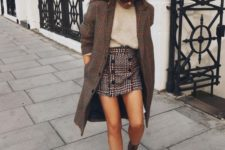 a tan cashmere top, a tweed mini skirt with buttons, colorful snake print boots and a plaid coat