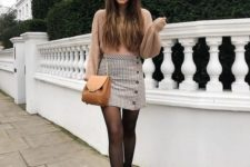 a tan sweater, a printed mini skirt with buttons, black combat boots and an amber crossbody
