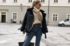 a tan sweater, blue cropped jeans, black combat boots, a black shearling coat and a dark bag