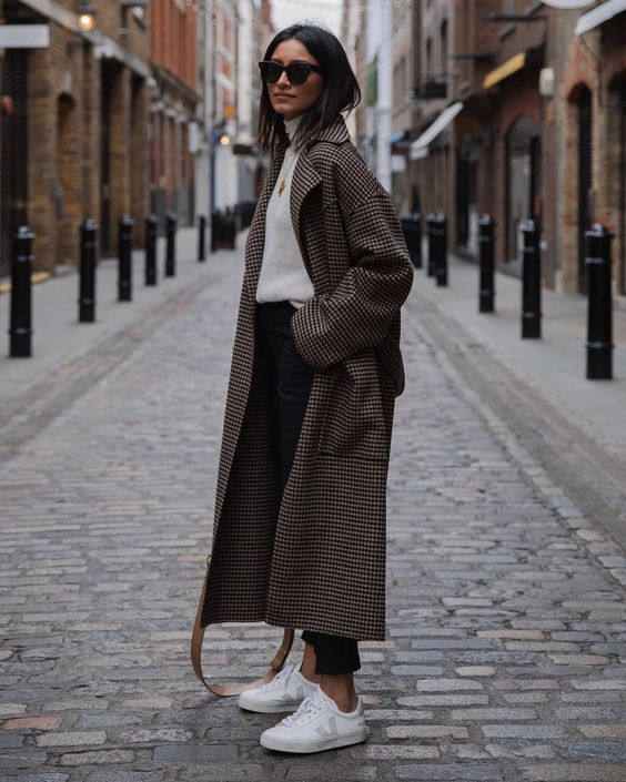 a white sweater, black jeans, a printed midi coat and white trainers for a comfy casual winter look