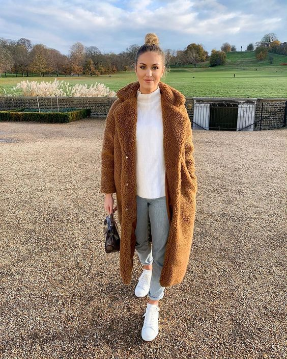 a white sweater, blue cuffed jeans, white sneakers, a brown teddy coat and a black bag