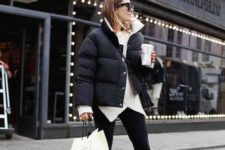 a white sweater with an assymetrical edge, black pants, white sneakers, a black and white puffed jacket