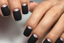 an elegant matte black manicure with shiny copper lines and moon detailing