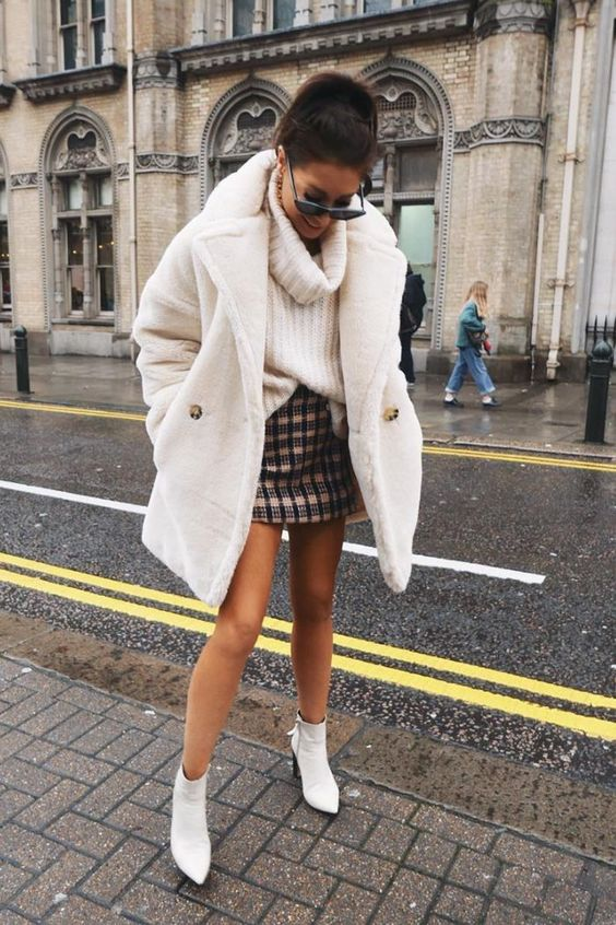 an oversized white chunky knit sweater, a tweed mini skirt, a white faux fur coat and white booties