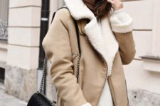 black leather leggings, an oversized white sweater, a tan shearling coat and a black bag