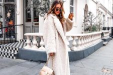blue skinnies, white trainers, a white fuzzy midi coat and a neutral bag for a chic and comfy outfit