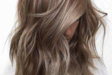 chestnut hair with mushroom blond balayage on an asymmetrical haircut with slight textures