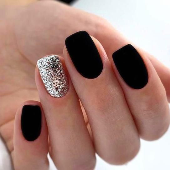 matte black nails paired with a single silver glitter accent nail for a chic and sparkly winter look