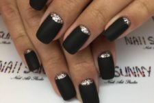 matte black nails with gold glitter half moon accents that make them really stand out and look wow