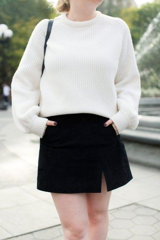 monochromatic look with a white sweater and a black denim mini with porckets plus a black bag