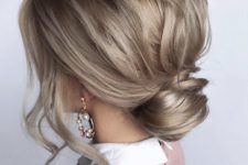 mushroom blond hair with waves made into a low bun with a messy top is a chic idea for every day