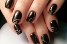 shiny black naiils with gold glitter stripes is a very creative and chic idea for a NYE party