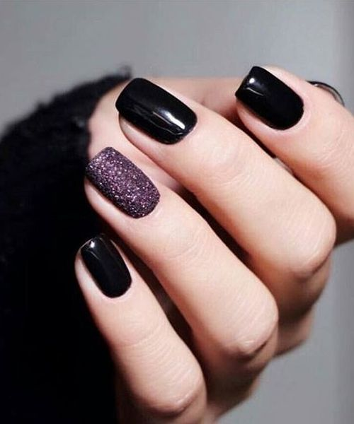 shiny black nails paired with a single mauve glitter accent one for a bolder and moodier look