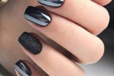 shiny black nails with a single black glitter one for a chic and refined accent