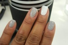 shiny grey nails paired with a white and a silver glitter one look holiday-like and very cute