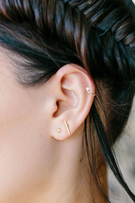 two gold studs paired with a single gold hoop with diamonds for a chic look