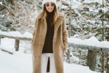 white jeans, a black turtleneck, brown moon boots, a brown teddy coat and a white beanie