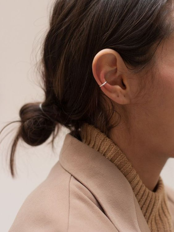 a minimalist silver ear hoop cuff with no earrings on is a trendy and edgy accent for a chic look