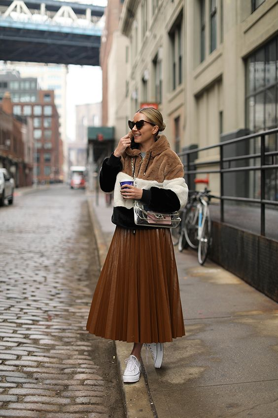 a rust-colored leather pleated midi skirt, a color block short faux fur coat and white sneakers for a trendy winter look