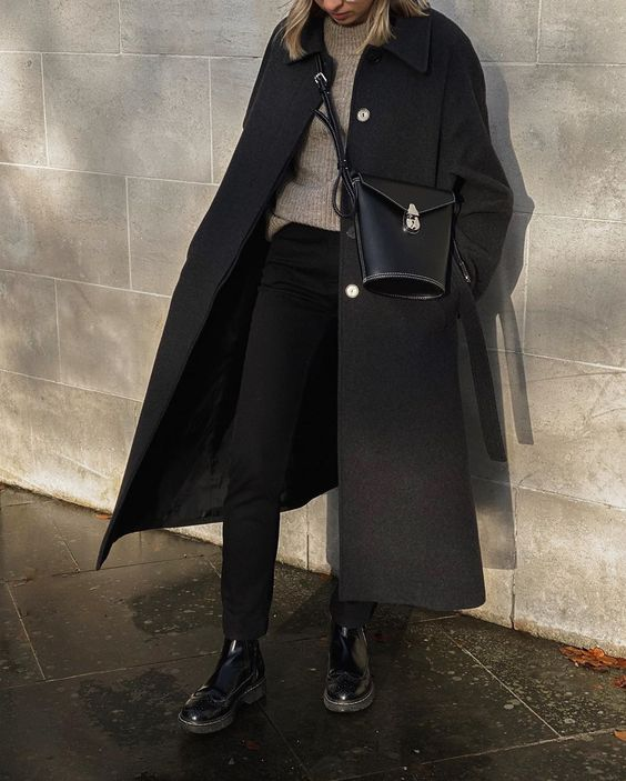 a neutral turtleneck, black jeans, a black midi coat, a black bucket bag and black chunky boots