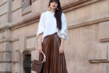 03 a rust-colored leather pleated midi, black sock boots and an oversized white sweater plus a bag on ring handles