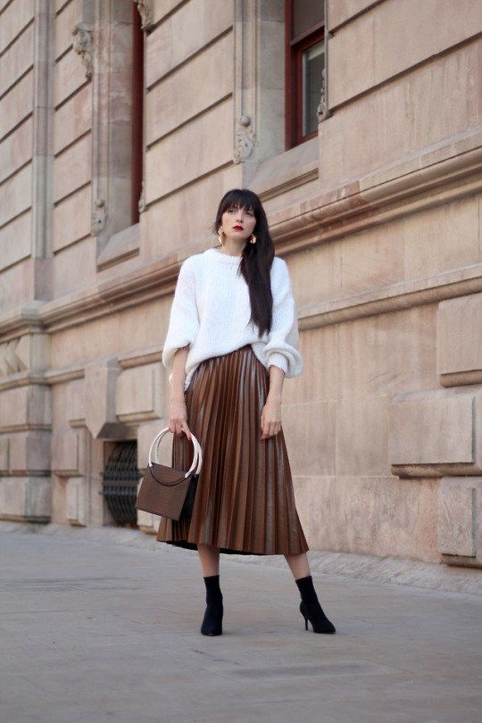 a rust-colored leather pleated midi, black sock boots and an oversized white sweater plus a bag on ring handles