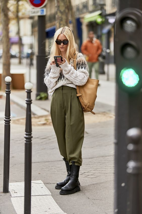 a printed oversized sweater, olive green oversized pants, chunky boots and an amber leather bag
