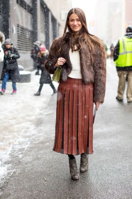 a winte rlook with a white top, a brown leather pleated midi, grey booties and a brown faux fur coat
