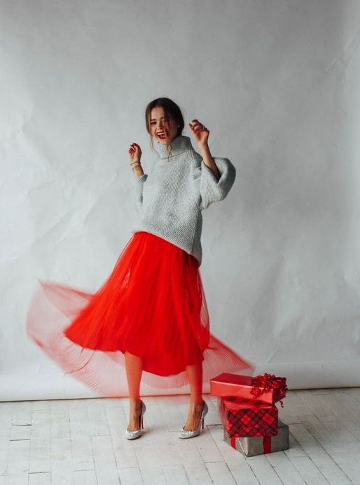 an oversized grey sweater, a layered red pleated midi skirt, silver heels for a bold holiday look